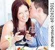 Happy boyfriend kissing his beautiful girlfriend during dinner at home - stock photo