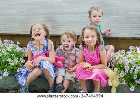 Happy boys and girls laughing and having fun on Easter while sitting outside in a garden eating candy during the spring season.   - stock photo
