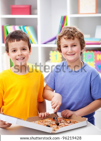 Happy boys cutting pizza in their room - stock photo