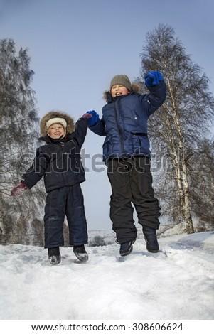 happy boys jump in winter outdoors - stock photo