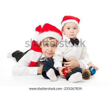 Happy boys kids brothers friends in santa's hats isolated on white, major brother holding hugging the junior, toddler playing with balls and golden cone - stock photo