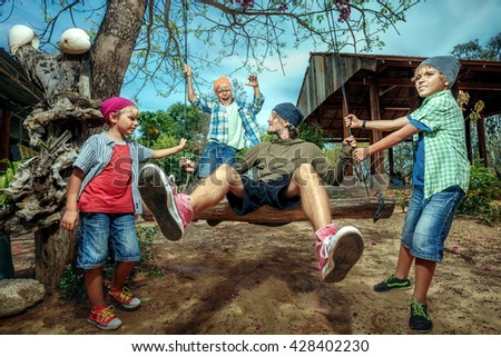 Happy boys pushing father on swing in playground - stock photo