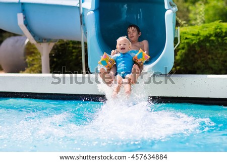 Happy boys, two brothers having fun together on water slide in a swimming pool during summer vacation in a beautiful tropical resort. Children sliding and playing in aqua park.  - stock photo