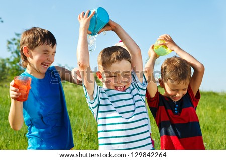Happy boys with plastic containers splashing water over one another's heads - stock photo