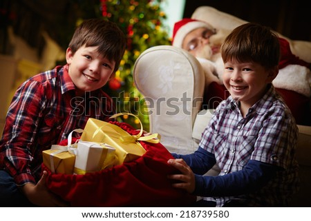 Happy boys with sack full of presents looking at camera with sleeping Santa Claus on background - stock photo