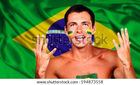 Happy brazilian fan celebrating over brazil flag background - stock photo