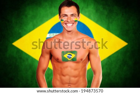 Happy brazilian fan standing over brazil flag background - stock photo