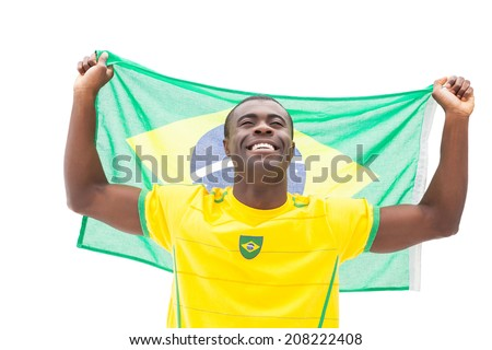 Happy brazilian football fan cheering holding flag on white background