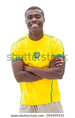 Happy brazilian football fan smiling at camera on white background