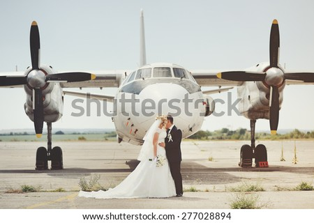 Happy bridal couple against old aircraft.  Wedding summer picture.  - stock photo