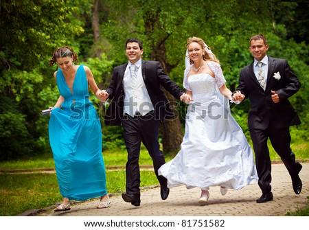 happy bride and bridegroom con frainds running along the alley in the park - stock photo