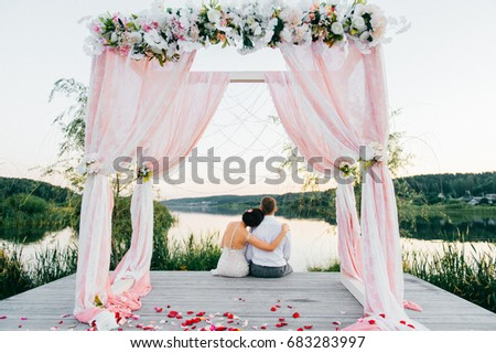 Happy Bride And Groom After Ceremony Sitting At Wooden Place For Wedding Arch With Decor