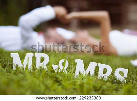 Happy bride and groom enjoying their wedding day in green nature, lying on grass - stock photo