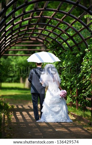 Happy bride and groom goes along the arch on wedding walk - stock photo