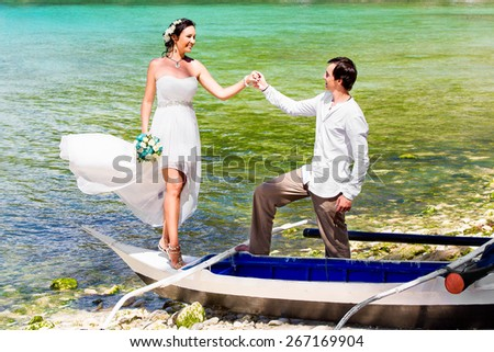 Happy bride and groom having fun on a tropical beach. Tropical sea in the background. Summer vacation concept. - stock photo
