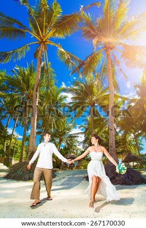 Happy bride and groom having fun on a tropical beach under the palm trees. Summer vacation concept. - stock photo