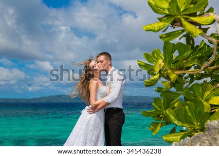 Happy bride and groom having fun on a tropical beach under the palm trees. Tropical sea in the background. Summer vacation concept. - stock photo