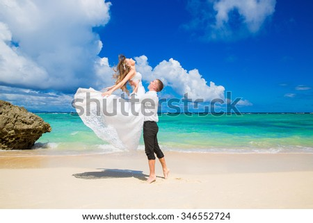 Happy bride and groom having fun on a tropical beach. Wedding and honeymoon on the tropical island. - stock photo