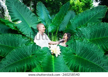Happy bride and groom having fun on a tropical jungle. Wedding and honeymoon on a tropical island. Summer vacation concept. - stock photo