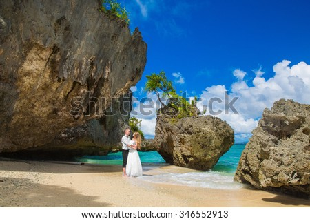 Happy Bride and Groom having fun on the tropical beach. Wedding and honeymoon concept.