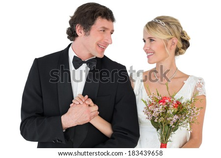 Happy bride and groom holding hands while looking at each other over white background - stock photo
