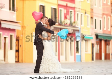 Happy bride and groom in Venice with balloons - stock photo