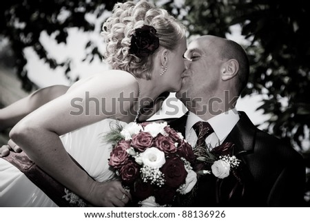 Happy bride and groom kissing outdoors - stock photo