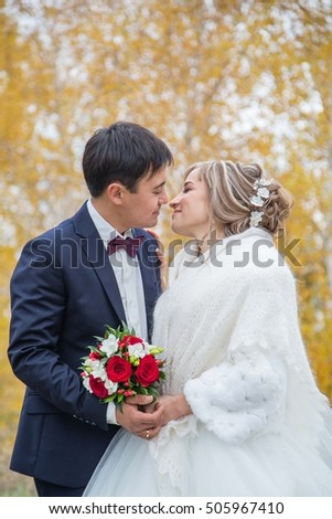 happy bride and groom look at each other, kiss each other on the background of the autumn forest, of the concept of love, affection, family