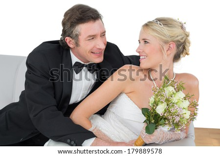 Happy bride and groom looking at each other while sitting on sofa at home - stock photo