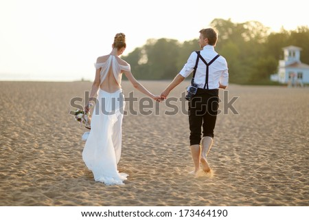 Happy bride and groom on a beautiful beach on sunset - stock photo