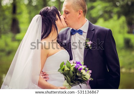Happy bride and groom on their wedding in europe . Beautiful wedding couple.Lovely couple kissing in the park. Marriage concept