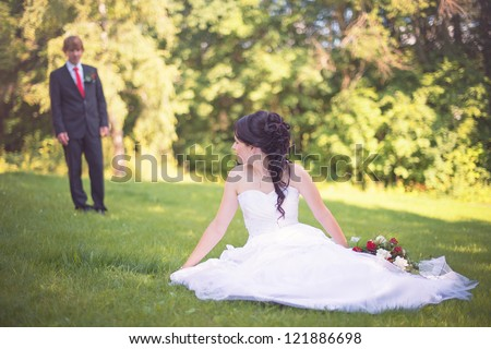happy bride and groom posing in the summer meadow