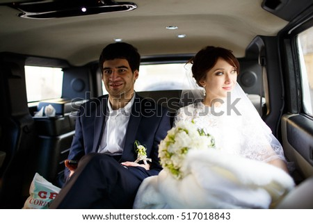 Happy bride and groom sitting in limousine