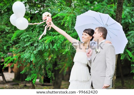 Happy bride and groom standing together in green autumn park holding white balloons in hand - stock photo