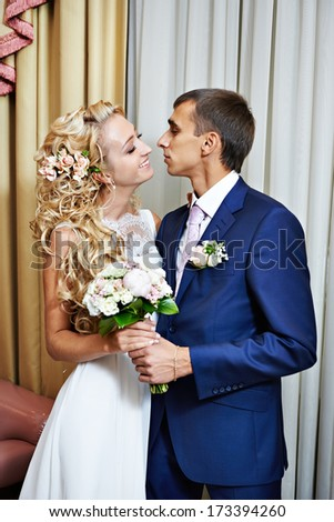Happy bride and groom together in interior - stock photo