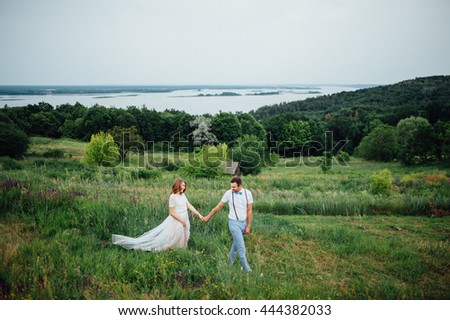 Happy Bride and groom walking on the green grass near the river, smiling and kissing