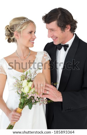 Happy bride and groom wearing wedding rings while looking at each other over white background - stock photo