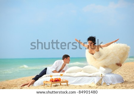 Happy Bride flying on bed to her husband on the beach - stock photo