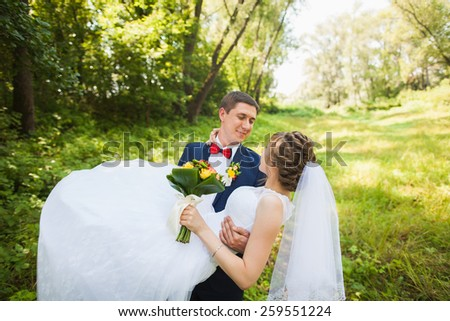 happy bride, groom holding hands in green park, kissing, smiling, laughing, embracing. lovers in wedding day. cheerful married couple in love. wedding concept. beautiful people. woman man - stock photo