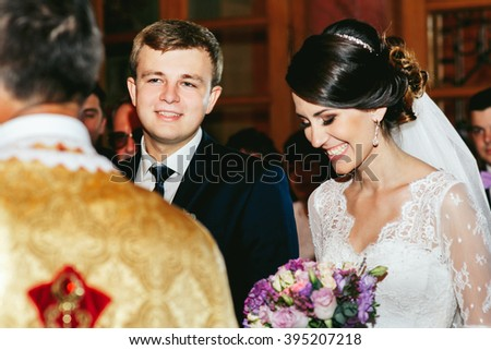 Happy bride & groom in christian church during wedding ceremony - stock photo