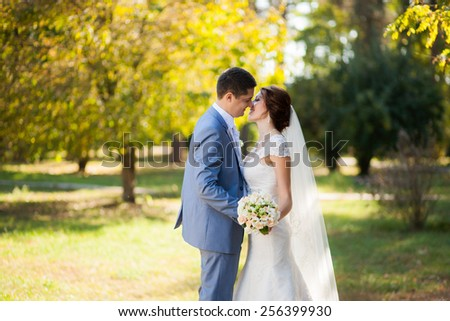 happy bride, groom standing in green park, kissing, smiling, laughing. lovers in wedding day. happy young couple in love. new family lifestyles. beautiful healthy people. nature background. woman man - stock photo