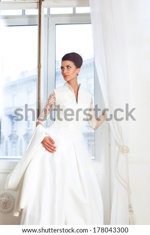 Happy bride in a wedding dress in the window