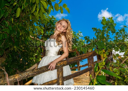 Happy bride in wedding dress smiles tropical plants in the background - stock photo