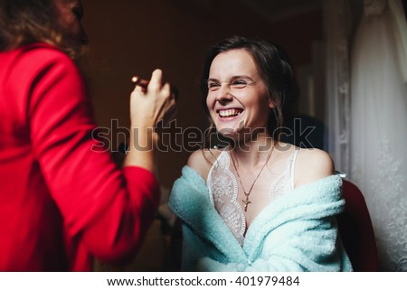 Happy bride is doing a make-up