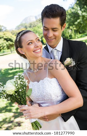 Happy bride looking at man while holding flower bouquet in park - stock photo