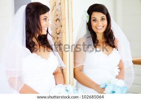 happy bride looking into mirror - stock photo