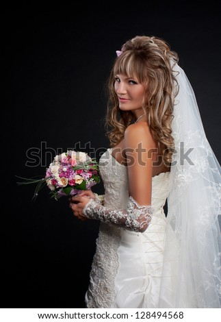 Happy bride on black background with bouquet of weddin - stock photo