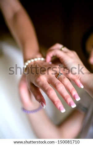 happy bride showing hands and jewelry on wedding dress on wedding day