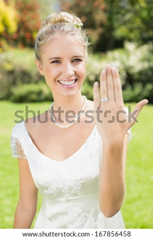 Happy bride showing her ring in the countryside - stock photo