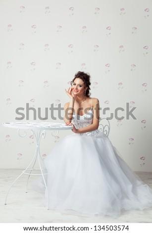Happy bride sitting in very beautiful dress, studio shot - stock photo